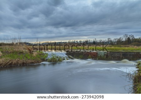 Thunderclouds over the river in the spring. The strong wind and clouds pass on the river. - stock photo