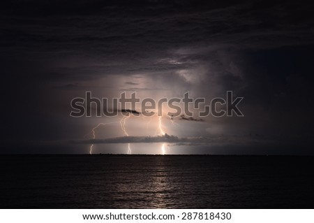 Thunderstorm and lightings in night over a sea with dramatic clouds