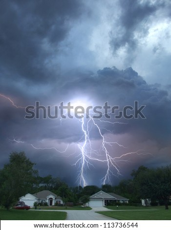 Thunderstorm and lightning over houses down the street - stock photo