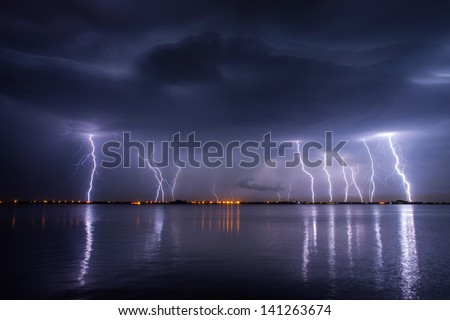 Thunderstorm and lightnings in night over a lake with reflaction - stock photo