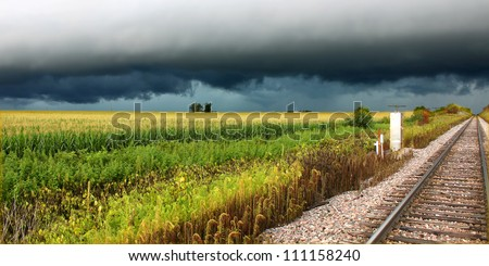Thunderstorm over railroad tracks and corn fields of northern Illinois - stock photo