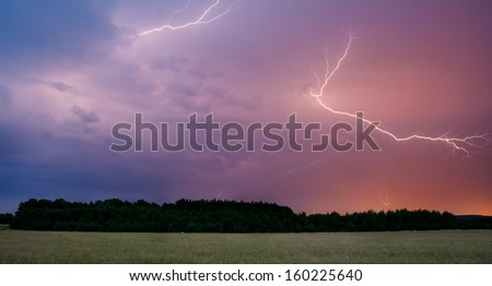 Thunderstorm with Lightning in Green Field - stock photo