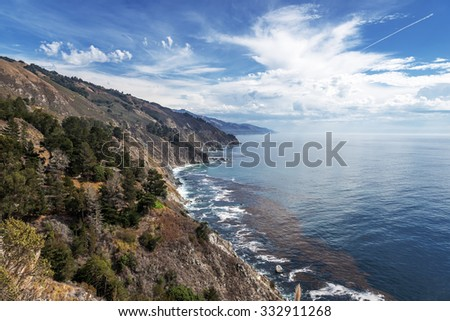 Thunderstorms, trees, waves splashing on huge rocks off shore, along a rocky coastline, fog & cloud covered mountain tops, traveling the Big Sur Highway (Highway) the California Central Coast. - stock photo
