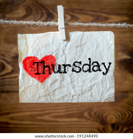 Thursday on red heart on aged paper hanging on the clothesline. On old wood background - stock photo