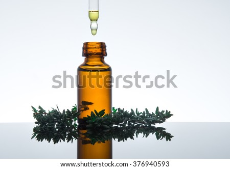 Thyme essential oil with thyme leaves, in amber glass bottle with dropper