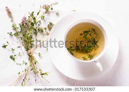 Thyme tea in a white cup on a white napkin. Top view. Selective focus ,