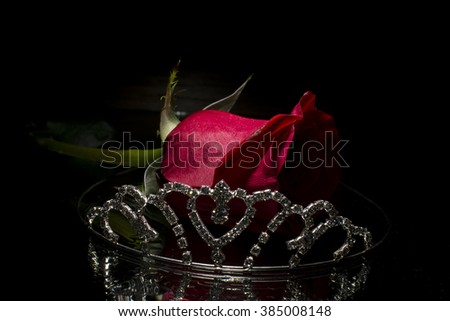 Tiara and red rose isolated on black background  - stock photo