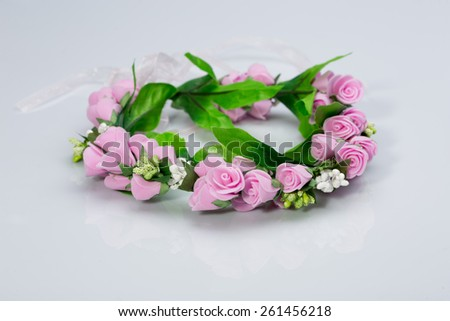 tiara of artificial  roses on a light background - stock photo
