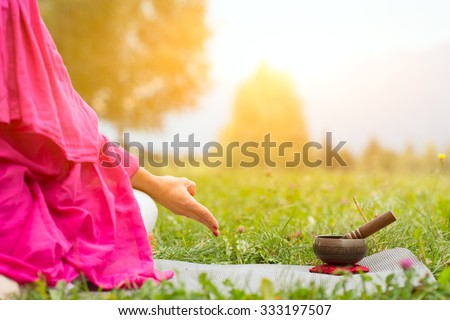 Tibetan bell beside yoga position in a meadow