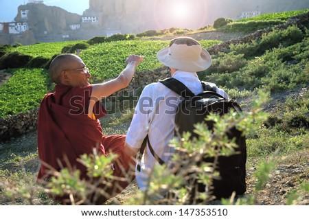 Tibetan monk discuss with European tourist in high mountains - stock photo