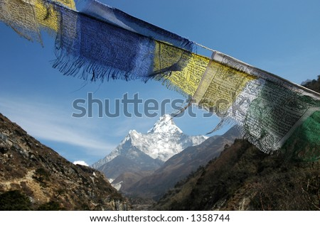 Tibetan prayer flags fluttering in the wind and mount Ama-Dablam in the background. - stock photo