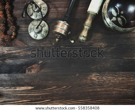 Tibetan religious objects for meditation and treatment on a wooden background, top view