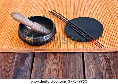 Tibetan singing bowl with its wooden mallet and incense sticks - stock photo