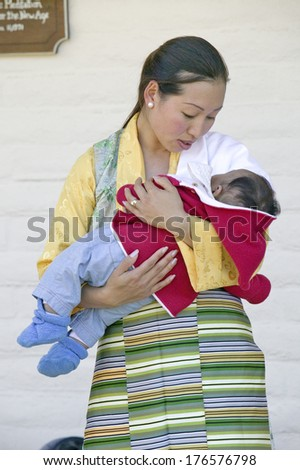 Tibetan woman in traditional dress holds child during Amitabha Empowerment Buddhist Ceremony, Meditation Mount in Ojai, CA