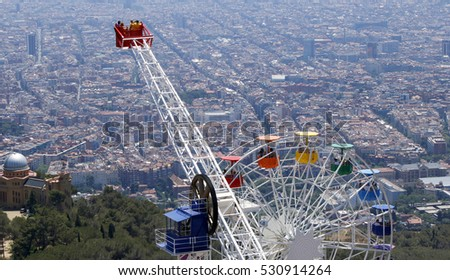 Tibidabo amusement park rides with people and ferris wheel, Barcelona, Catalonia, Spain, July 2016
