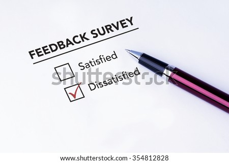 Tick placed in dissatisfied check box on feedback survey form with a pen on isolated white background. Business concept survey.