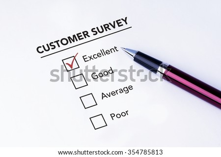 Tick placed in excellent check box on customer service satisfaction survey form with a pen on isolated white background. Business concept survey.
