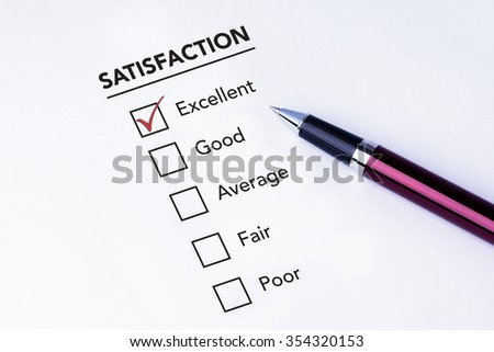 Tick placed in excellent check box on service satisfaction survey form with a pen on isolated white background. Business concept survey.