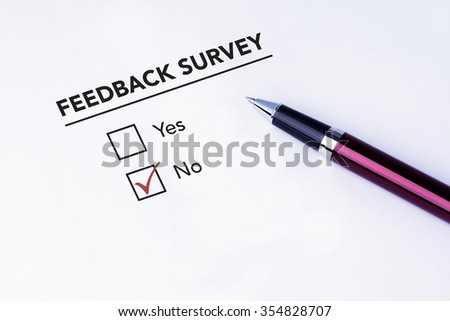 Tick placed in no check box on feedback survey form with a pen on isolated white background. Business concept survey.