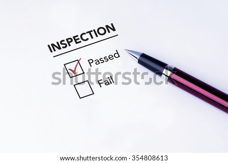 Tick placed in passed check box on inspection form with a pen on isolated white background. Business concept survey.
