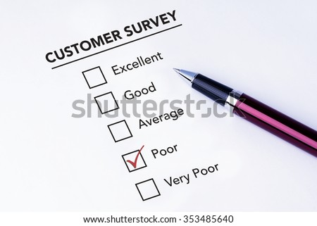 Tick placed in poor check box on customer service satisfaction survey form with a pen on isolated white background. Business concept survey. - stock photo