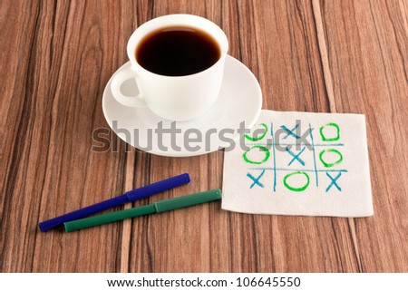 Tick-tack-toe on a napkin and cup of coffee - stock photo