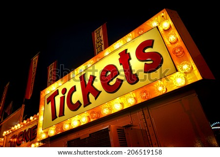 Tickets advertising neon sign with bright yellow lights marquee above carnival ticket counter booth and distributor vending machine at a festive county fair at night - stock photo