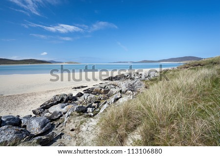Tidal beach of Luskentyre, Isle of Harris, Outer Hebrides, Scotland. It's famous for the beautiful white sandy beach which runs for miles and the gorgeous green-blue waters lapping up onto its shores - stock photo