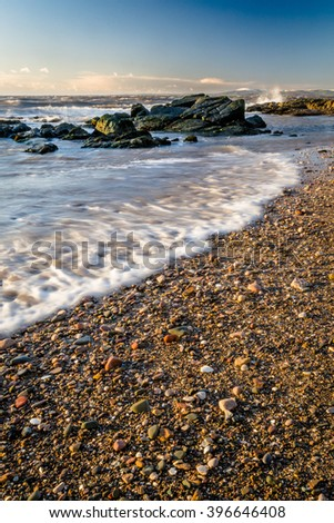 Tide coming in on pebble beach on the Western shore of England. - stock photo