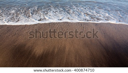 tide flowing over black sand at a surf beach, Gisborne, New Zealand  - stock photo