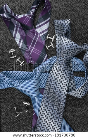 Tie and cufflinks lying on the skin, can be used as background - stock photo