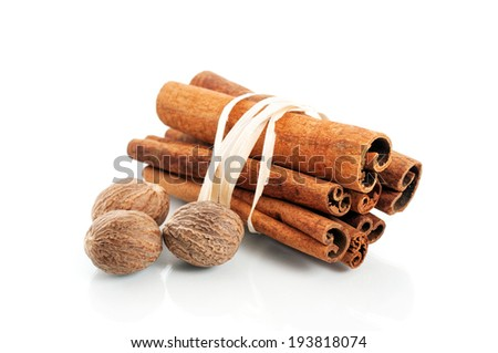 Tied cinnamon sticks and nutmeg over white - stock photo