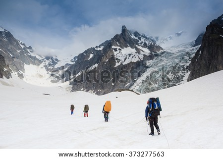 Tied climbers climbing mountain with snow field