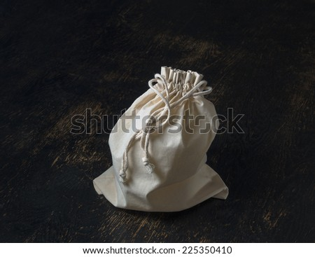 tied closed drawstring bag on wood table - stock photo