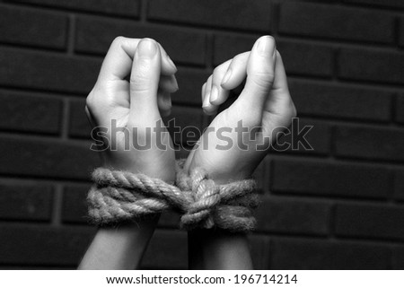 Tied hands in shades of grey - stock photo