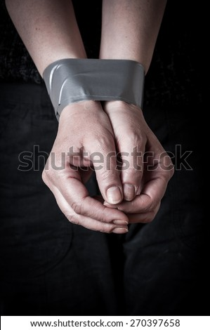 Tied hands of a trapped and abused woman. Low key