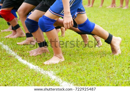 Tied leg run race, Funny run game, group of sportsmen are tied their legs together and run to finish point