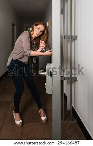 Tied to the office - Attractive business woman is strapped to metal office doors with handcuffs - trying to free herself in panic
