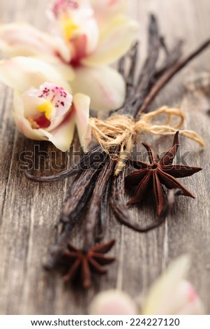 Tied vanilla pods and orchid flowers on old wooden table. - stock photo