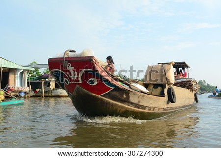 TIEN GIANG PROVINCE, VIETNAM - FEB 11, 2015: A boat carry goods at Cai Be Floating Market. Cai Be Market is one of most famous floating market in Vietnam.