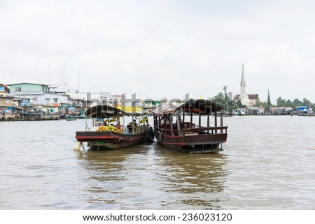 Tien Giang, Vietnam - Nov 28, 2014: Boat filled with fruits, vegetables and other products on sale on Cai Be floating market on Tien river, border between Tien Giang, Vinh Long and Ben Tre Provinces