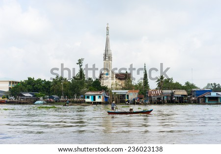 Tien Giang, Vietnam - Nov 28, 2014: Tien river scene in Mekong Delta, with rowing boats and church on background - stock photo