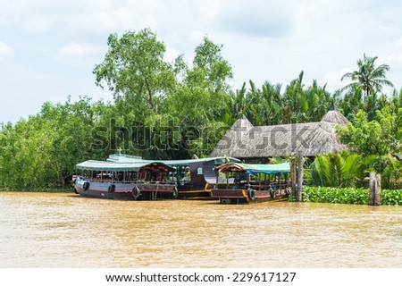 TIEN GIANG, VIETNAM - OCT 5, 2014: Wooden boat on Mekong river in Southern Vietnam. Mekong is the 12th-longest river and flows trough China, Burma, Laos, Thailand, Cambodia, Vietnam