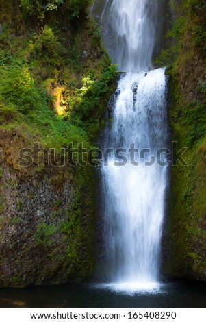 Tiered waterfalls cascading together into a lower pool. - stock photo
