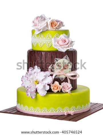 Tiered wedding cake with roses. Decorations on the wedding theme.