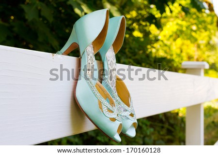Tiffany blue wedding shoes with heels are hanging on a white fence before the bride puts them on for her wedding ceremony. - stock photo
