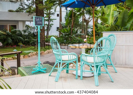 Tiffany coloured chairs standing outside on the veranda in the restaurant - stock photo