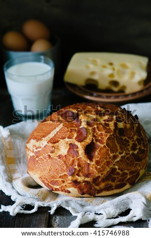 Tiger bread on a wooden table with milk, eggs and cheese in a rustic style