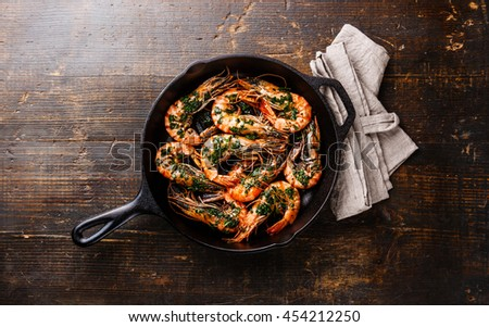 Tiger prawns roasted on frying grill pan with green sauce and lemon on wooden background - stock photo