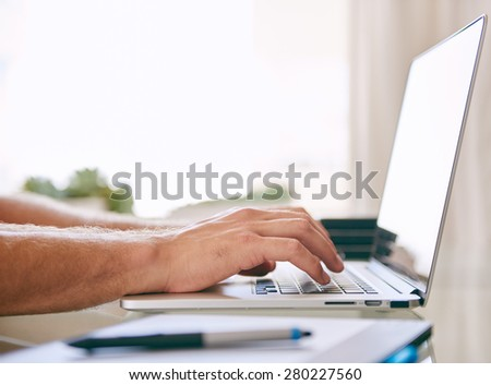 tight crop horizontal image of hands typing on a laptop with a stylus resting on a tablet in the foreground and copy space - stock photo